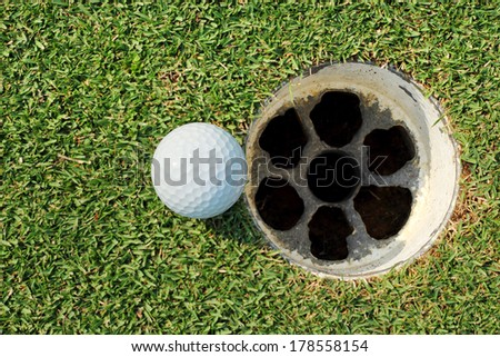 golf ball on lip hole  - stock photo