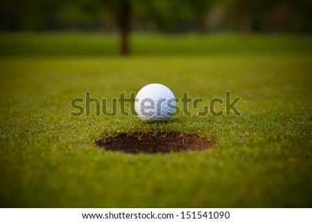 golf ball on lip of cup. - stock photo