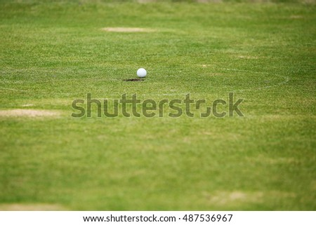 Golf ball on lip of cup,hole