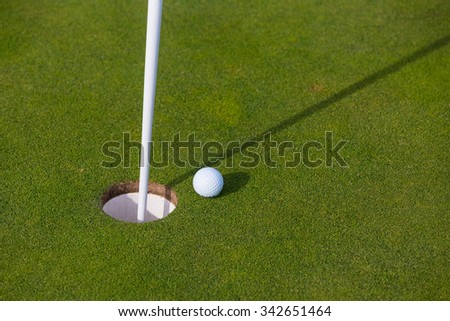 Golf ball on lip of cup on the green golf course - stock photo