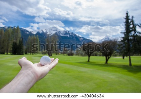 Golf ball on mans hand on golf course in Alps in summer.  - stock photo