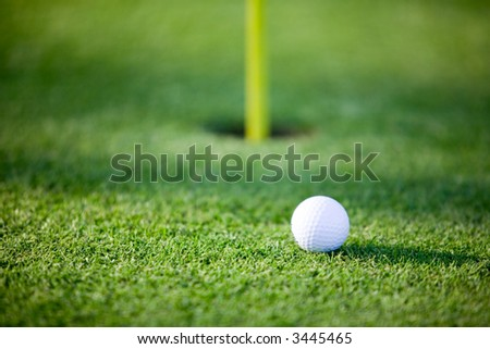 Golf ball on putting green, shallow focus on ball