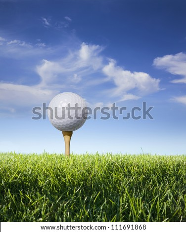 Golf ball on tee against blue sky and clouds