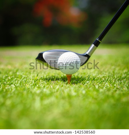 Golf ball on tee in front of driver - stock photo