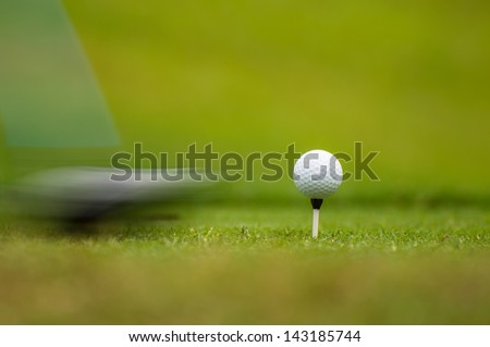 Golf ball on tee off before the game. - stock photo