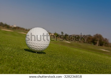 Golf ball on tee off zone with blurred golf course background. - stock photo