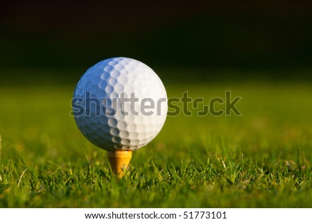 Golf ball on tee on manicured golf course grass - stock photo