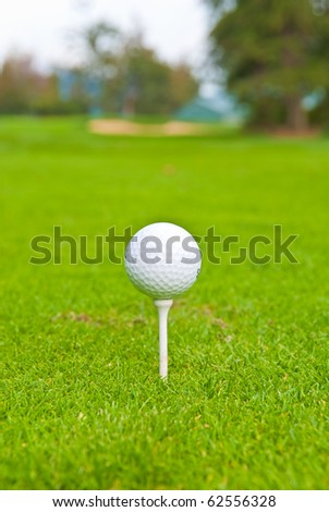 Golf ball on tee over a blurred green. Shallow depth of field. Focus on the ball. - stock photo