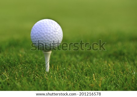 Golf ball on tee over a green background - stock photo