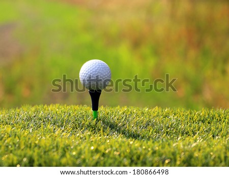Golf Ball on tee over green grass - stock photo