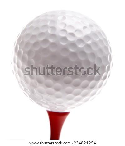 Golf ball on tee. Plain background - stock photo