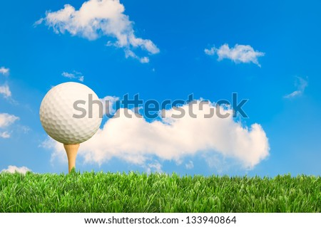 Golf ball on tee with blue sky background - stock photo