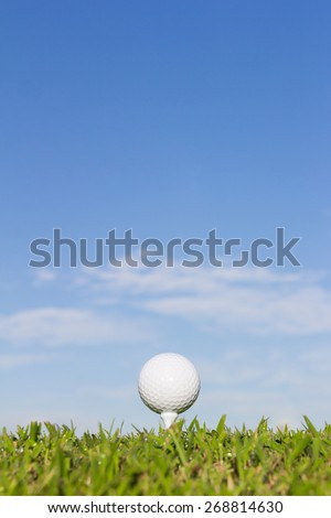 Golf ball on tee with sky background - stock photo