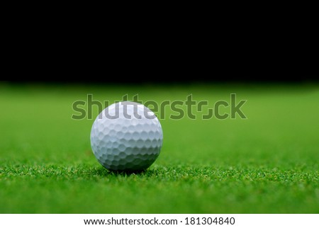 Golf ball on the green, blurred background - stock photo