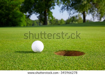 Golf ball on the green close to the hole - stock photo
