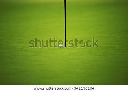 Golf ball on the hole, luxury golf field  - stock photo
