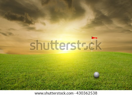 Golf ball on the lawn and blurred sky-clouds and sunlight - stock photo