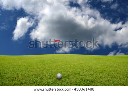 Golf ball on the lawn and blurred sky-clouds background.