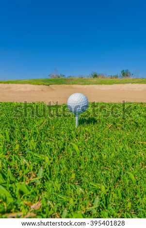 Golf ball on the tee at the beautiful golf course. - stock photo