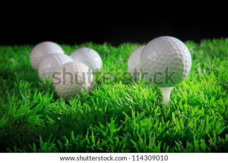 golf ball on white tee with green grass field - stock photo