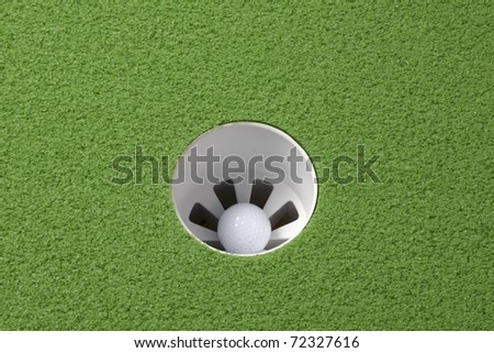Golf ball sits in the hole on golf course, includes space for copy