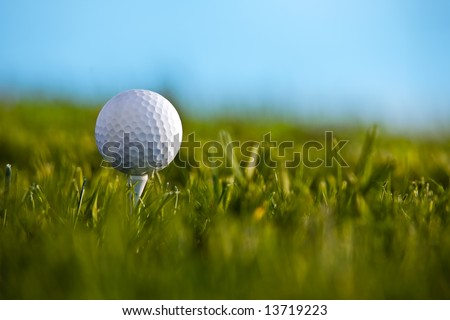 Golf ball sitting on tee with blue sky and grass background.
