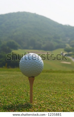 golf ball teed up for hitting with a driver - stock photo