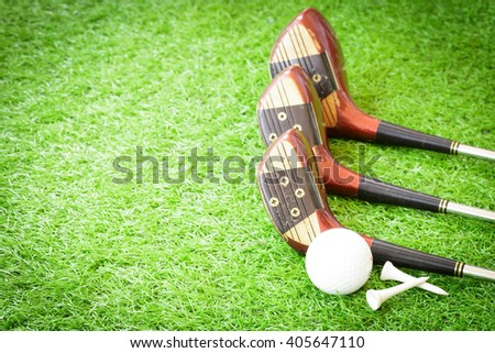 Golf ball, tees and old wood golf clubs on green grass background. - stock photo