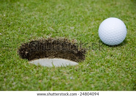 Golf ball very close to a hole - stock photo