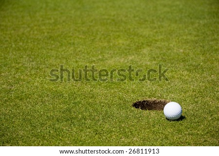 Golf ball very close to a hole on a putting green