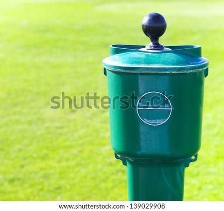 Golf ball washer over green baackground. Close up - stock photo