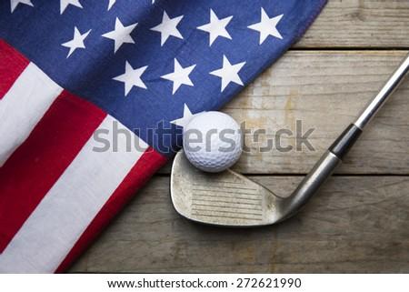 Golf ball with flag of USA on wood table - stock photo