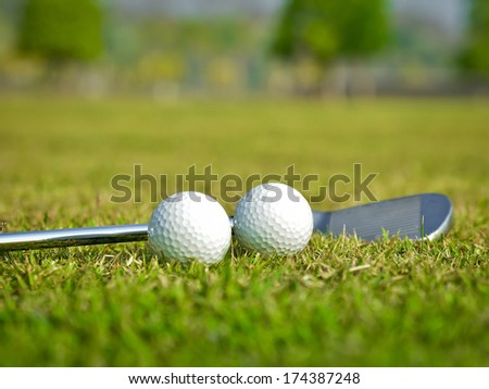 Golf ball with golf club on green grass