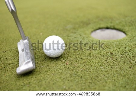 golf ball with iron and hole on a golf course