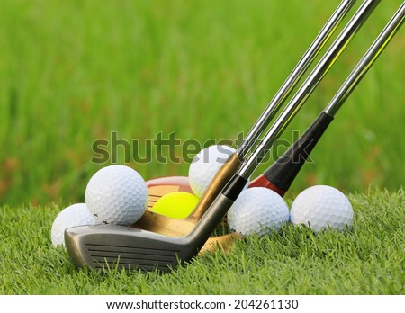 Golf balls and  Drivers on green grass background - stock photo