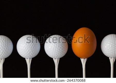 Golf balls and egg on a black glass table