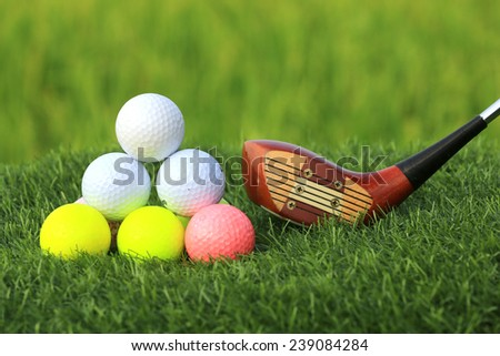 Golf balls and Wooden Driver on green grass background - stock photo