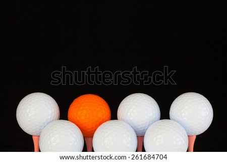 Golf balls and wooden tees on a black background