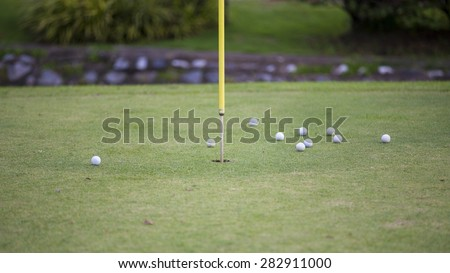 Golf balls in practice hole with flag marking the hole - stock photo