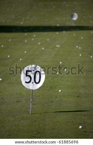 Golf balls lying on a golf driving range with a 50 meter/yard sign - stock photo