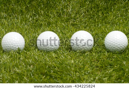 Golf balls on green grass. - stock photo