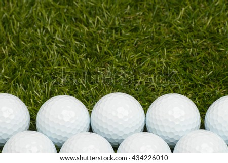 Golf balls on green grass arranged at the bottom. Room for text at the top. - stock photo