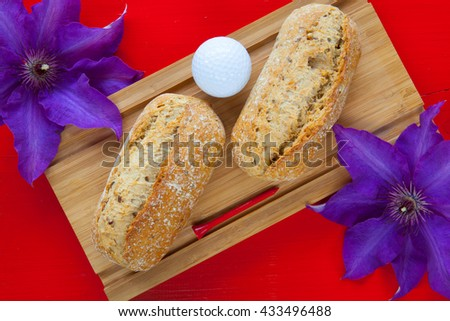 Golf breakfast - Two wheat bread and golf ball on wooden desk - stock photo
