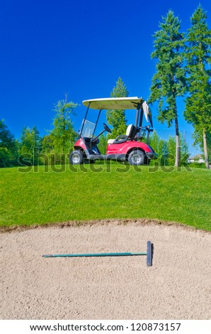 Golf cart at the golf course in front of the sand bunker
