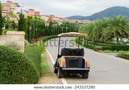 Golf cart or club car park on the way to modern village. - stock photo