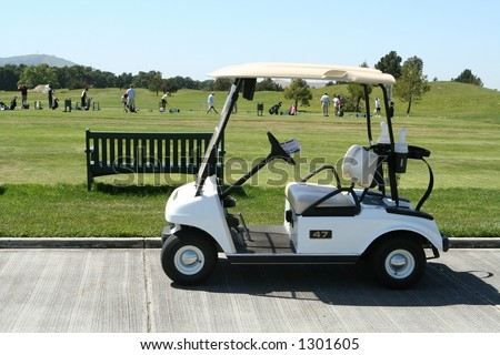 Golf cart with golfers in background