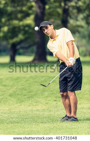 Golf Chipping - Golfer playing a chipping shot. - stock photo