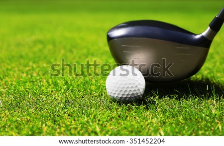 Golf club and ball on a green grass - stock photo