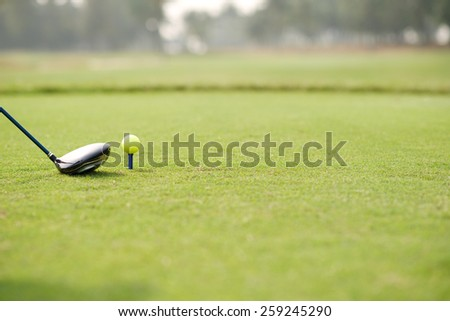 Golf club and ball on a tee, selective focus - stock photo