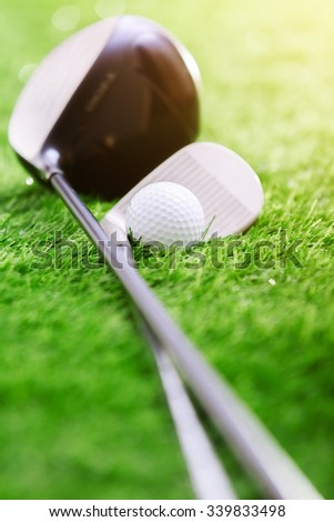 Golf club and ball on green grass - stock photo